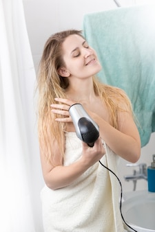 Bella donna ricoperta di telo da bagno con asciugacapelli in bagno