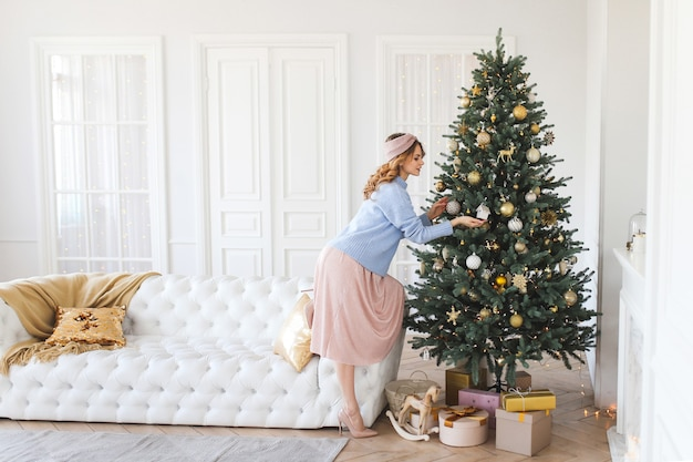 Bella donna in un maglione accogliente decora l'albero di natale e celebra le vacanze a casa