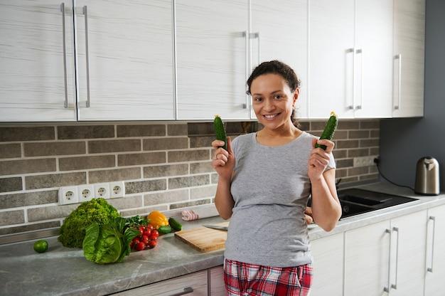 Bella donna carina sorride con il sorriso a trentadue denti alla fotocamera mentre prepara una sana insalata cruda vegana in cucina. concetto di stile di vita sano.