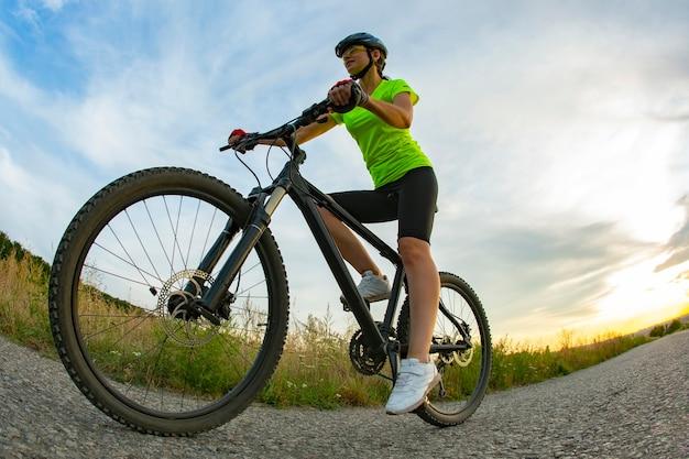 Il ciclista della bella donna guida una bicicletta sulla strada. stile di vita sano e sport. tempo libero e hobby