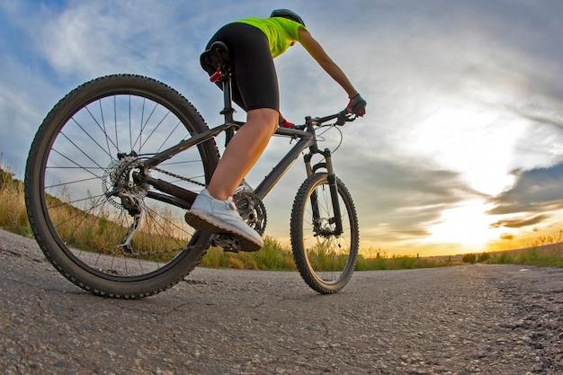 Bella donna ciclista va in bicicletta sulla strada al tramonto. stile di vita sano e sport. tempo libero e hobby
