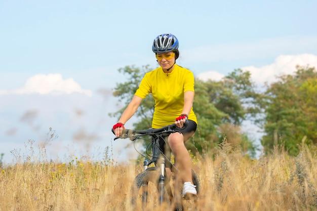 Bella donna ciclista cavalca sul campo in bicicletta. stile di vita sano e sport. tempo libero e hobby