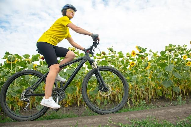 Il ciclista della bella donna guida un campo con i girasoli su una bicicletta. stile di vita sano e sport. tempo libero e hobby