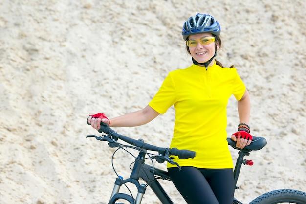 Bella donna ciclista con una bicicletta sulla natura