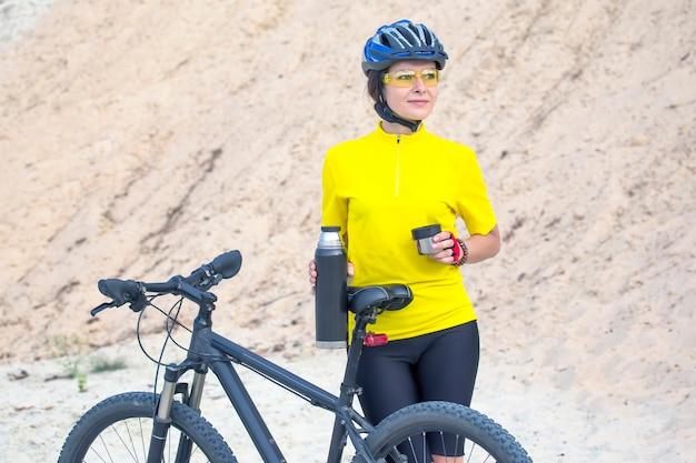 Bella donna ciclista in giallo con tè e thermos in mano