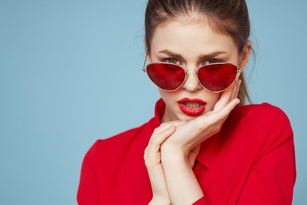 Bella donna in occhiali scuri camicia rossa trucco luminoso emozioni sguardo attraente spazio blu.