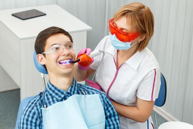 Dentista di bella donna che cura i denti di un paziente in studio dentistico. dottore con occhiali, maschera, divisa bianca e guanti rosa. odontoiatria