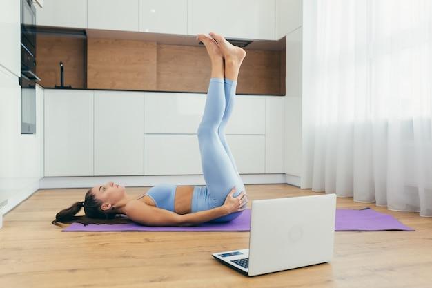 Bella donna facendo fitness a casa in linea con il computer portatile