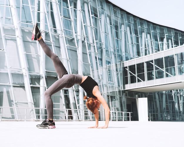 Bella donna che fa esercizi di stretching yoga fuori in città