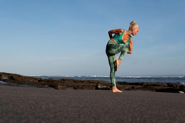 Bella donna che fa yoga sulla spiaggia