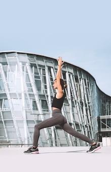 Bella donna che fa esercizi di yoga fuori città ragazza che pratica yoga all'aperto
