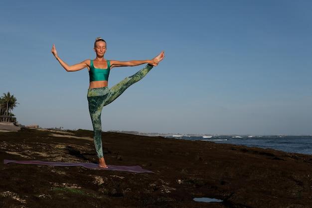 Bella donna che fa yoga. piano intermedio