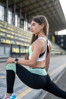 Bella donna che fa le pose di yoga su uno stadio della città. concetto di stile di vita sano