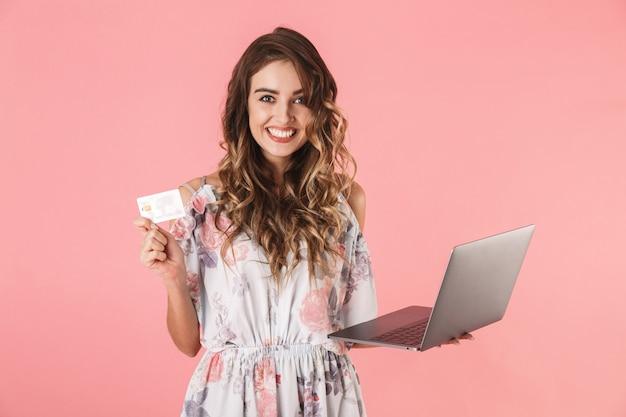 Bella donna in vestito che tiene laptop d'argento e carta di credito, isolata sul rosa