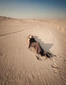 Bella donna in abito sdraiato sulla duna di sabbia al deserto