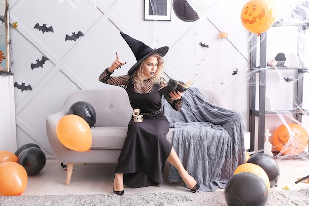 Bella donna vestita da strega per halloween a casa