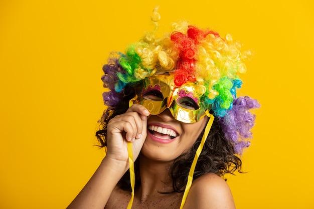 Bella donna vestita per la notte di carnevale. donna sorridente pronta a godersi il carnevale con una parrucca e una maschera colorate