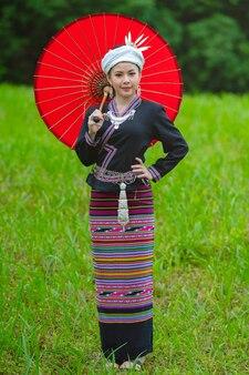 La bella donna si è vestita in costume tradizionale con l'ombrello rosso