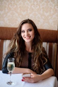 Bella donna che beve champagne e parla al telefono nel ristorante