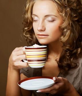 Bella donna che beve caffè. girato in studio.