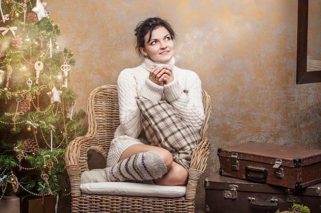 Bella donna che beve tè o caffè seduta su una sedia con cuscini all'interno di natale