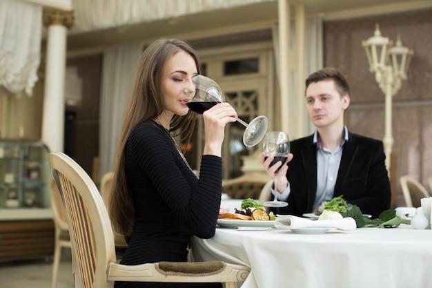 Bella donna che beve vino al ristorante