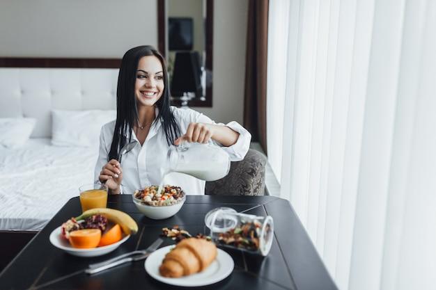 Bella donna che mangia prima colazione nella camera di albergo. lei sorride e guarda fuori dalla finestra