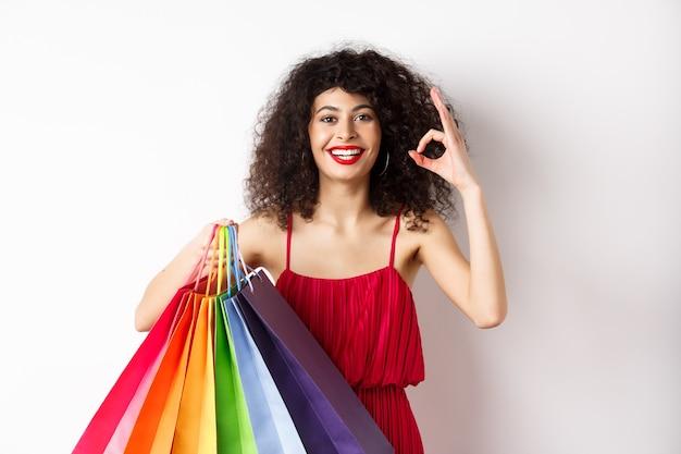 Bella donna in abito elegante, tenendo le borse della spesa e mostrando segno ok, consiglia negozio con sconti, sfondo bianco.