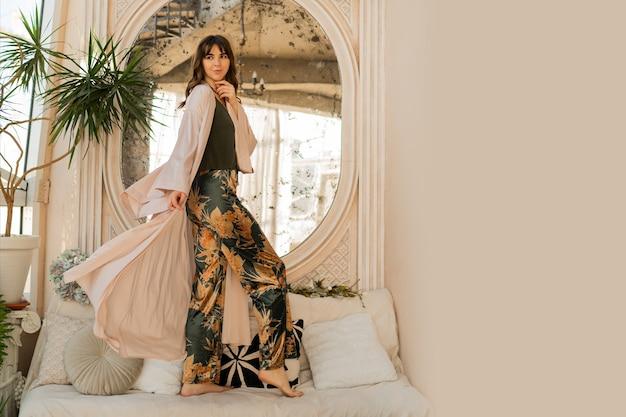 Bella donna in abbigliamento da donna elegante in posa in eleganti interni bohémien.