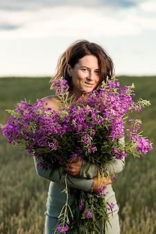 Bella donna godendo l'aroma di un bouquet di fiori di lupini viola in un campo di fiori