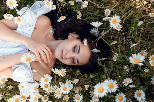 Bella donna che gode del campo, bella ragazza con i capelli scuri rilassante all'aperto, divertirsi, tenendo la pianta, felice giovane donna e natura verde primavera, concetto di armonia