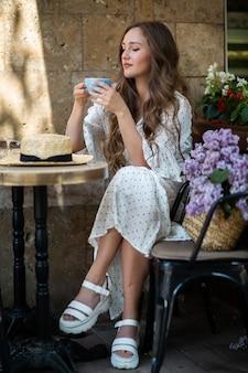 Bella donna che gode del caffè del mattino vicino al fiore lilla. modello carino e fiori. aromaterapia e concetto di primavera. la ragazza beve il caffè alla caffetteria.