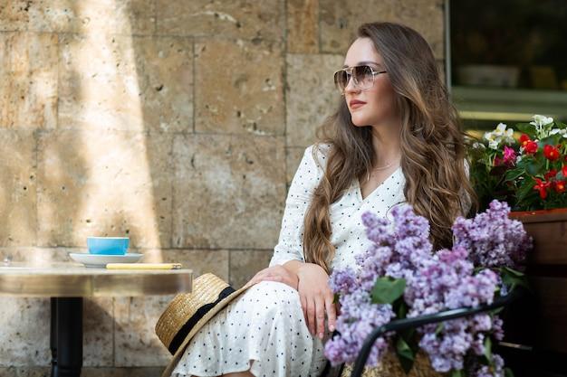 Bella donna che gode della mattina vicino al fiore lilla. modello carino e fiori. aromaterapia e concetto di primavera. ragazza in caffetteria. siediti con un cesto di lillà nelle mani. floristica