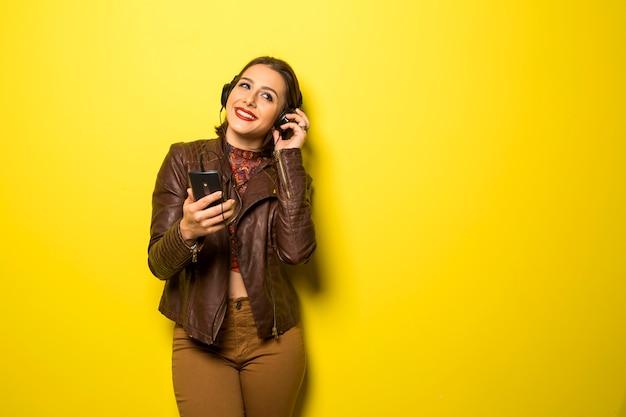 Bella donna che gode della musica con le cuffie nella parete gialla