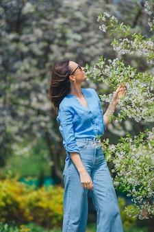 Bella donna che gode dell'odore nel giardino di ciliegie di primavera