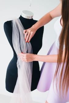 Una bellissima donna-stilista, designer, stenditura di tessuti su un manichino su misura. il lavoro di una stilista femminile. il processo di lavoro come stilista.