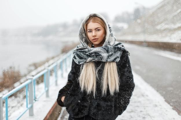 Bella donna in sciarpa alla moda di moda in inverno nevoso giorno