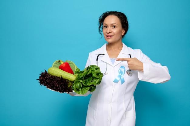 Bella donna, nutrizionista medico femminile che indossa un abito medico bianco con punti di nastro blu di consapevolezza su un piatto pieno di cibo vegano crudo sano. concetto di giornata mondiale del diabete con spazio per la pubblicità