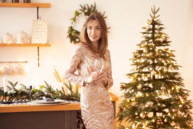 Una bella donna in un abito festivo con un bicchiere in mano si trova vicino al tavolo sullo sfondo di un albero di natale e di una ghirlanda. celebrazione del nuovo anno, festa. focalizzazione morbida. banner orizzontale.