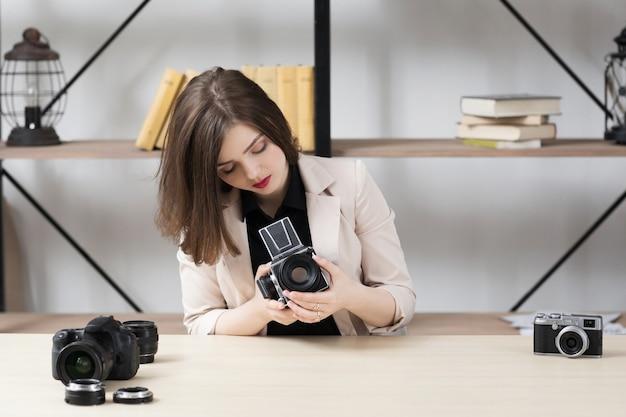 Bella donna che fissa retro macchina fotografica.