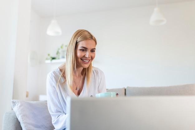 Bella donna freelance che annota le informazioni per la pianificazione del progetto facendo un lavoro remoto tramite computer portatile. ragazza che ride durante la lettura della posta elettronica sul moderno dispositivo portatile.