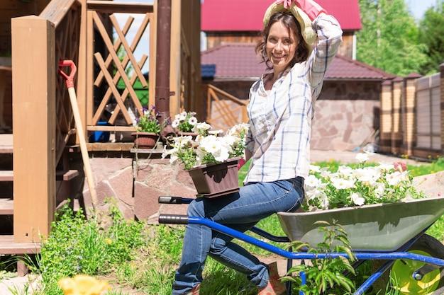 Giardiniere della bella donna con i fiori. pianta piantine nel giardino di casa. il contadino tiene i germogli nelle sue mani.