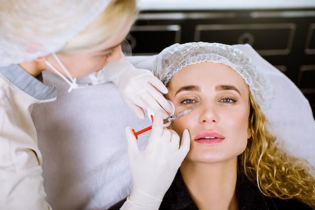 La bella donna ottiene iniezioni. cosmetologia. beauty face. chiuda sul ritratto della donna bionda con le mani femminili del cosmetologo vicino al suo fronte