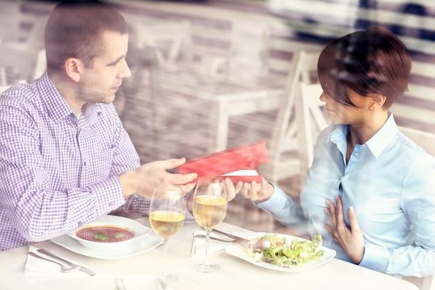 Una bella donna che riceve un regalo dal marito in una foto di un ristorante scattata attraverso una finestra
