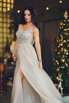 Bella donna ragazza in studio di capodanno in posa, foto sessione di foto di capodanno. bella ragazza in un vestito lussuoso con gambe snelle. natale, inverno, concetto di felicità.