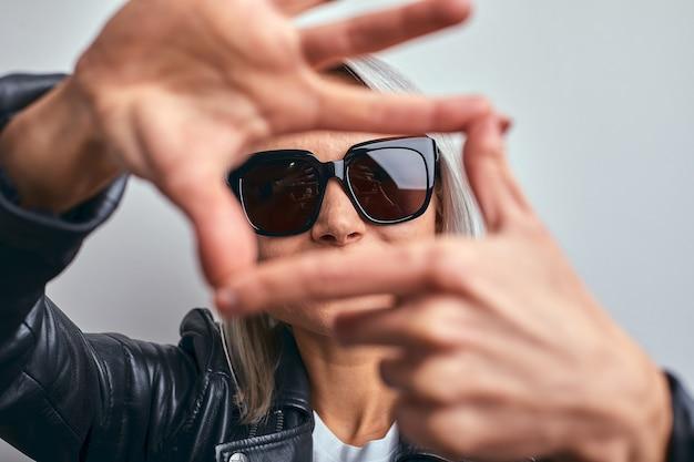 Bella donna con gli occhiali, in una giacca di pelle nera su sfondo grigio, che fa una cornice usando le mani con i palmi e le dita, prospettiva della fotocamera.