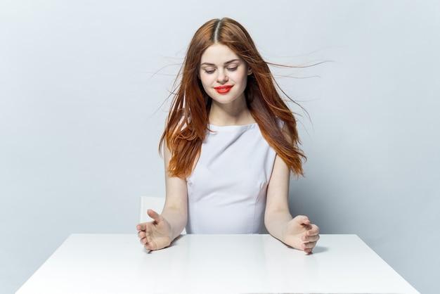 Bella donna con gli occhiali si siede a un tavolo, parete leggera, posa emozioni