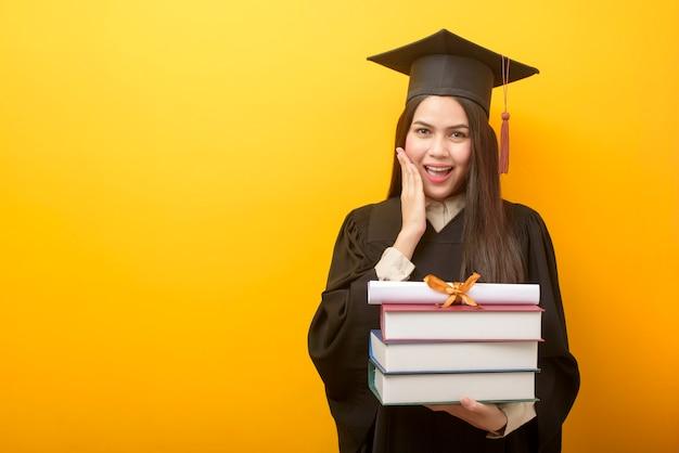 La bella donna in abito da laurea tiene in mano libri e certificato su giallo