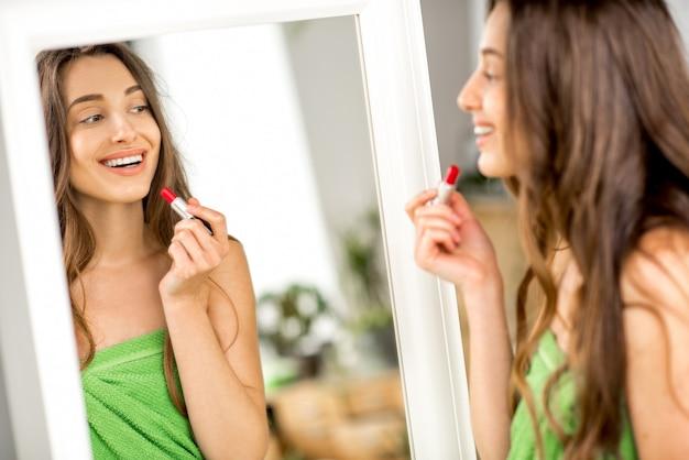 Bella donna in labbra di pittura asciugamano verde guardando lo specchio in bagno. truccarsi con il rossetto