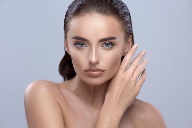 Bella donna su sfondo grigio, esaminando la fotocamera, primo piano della ragazza di bellezza, modella bruna con il braccio che tocca, bel viso con il braccio
